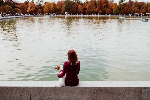 Giovane donna e simpatico cane sul lago in un parco urbano. parco del retiro a madrid