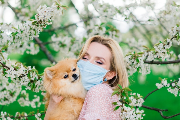 Giovane donna e spitz rosso con una maschera medica sul viso sulla natura in una giornata di primavera. pandemia di coronavirus