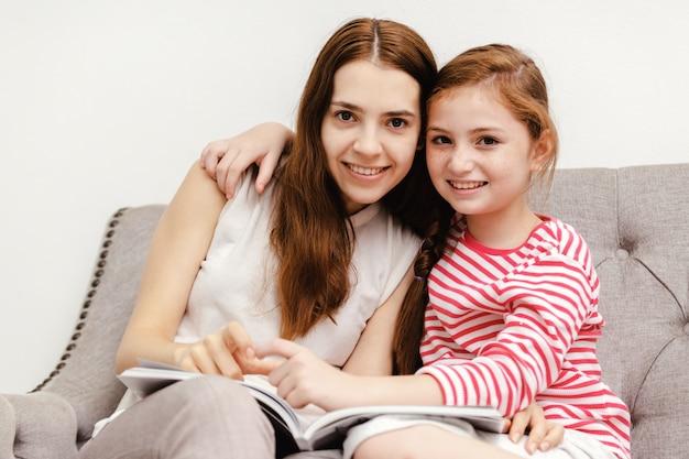 Giovane donna e sua figlia della bambina che si siedono libri di lettura sul divano a casa