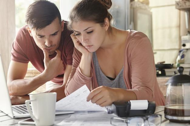 Giovane donna e suo marito disoccupato con molti debiti che fanno insieme in cucina il lavoro di ufficio