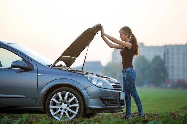 Giovane donna e un'auto con cappuccio scoppiato. trasporti, problemi dei veicoli e concetto di guasti.