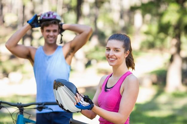 Giovane donna e uomo con le biciclette nella foresta