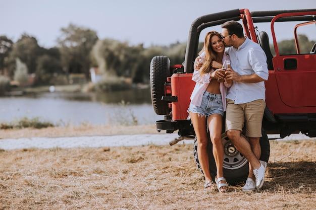 Giovane donna e uomo divertirsi all'aperto vicino auto rossa al giorno d'estate