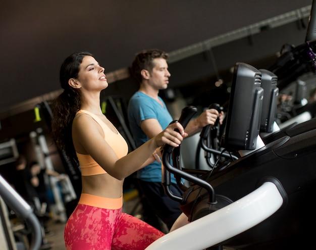 Giovane donna e uomo su ellittica stepper trainer che esercitano in palestra