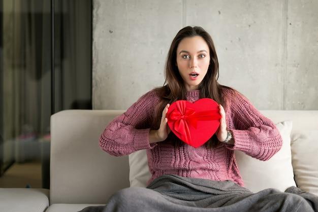 Giovane donna eccitata e sorpresa in possesso di un regalo a forma di cuore dal suo fidanzato