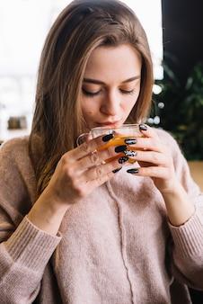 Giovane donna elegante che beve dalla tazza in caffè