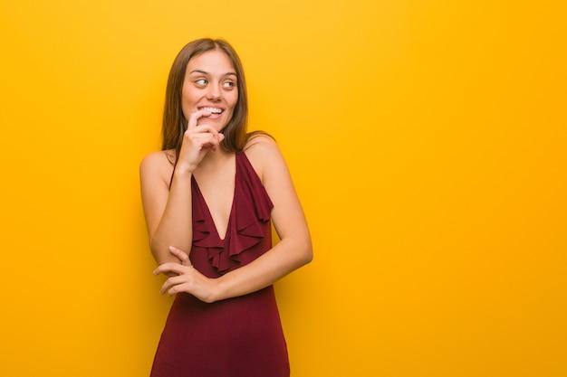 Giovane donna elegante che indossa un abito rilassato pensando a qualcosa guardando uno spazio di copia