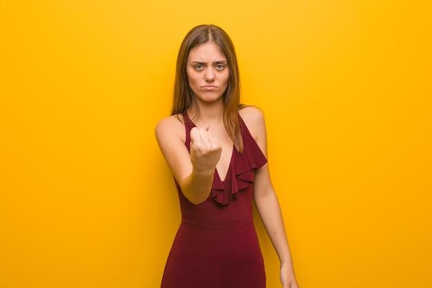 Giovane donna elegante che indossa un vestito che mostra il pugno di fronte, espressione arrabbiata