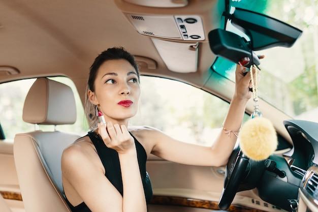Giovane donna elegante che osserva nello specchio di vista dell'automobile mentre si applica