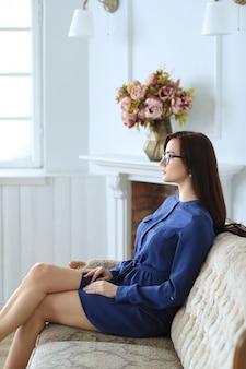 Giovane donna elegante che posa a casa