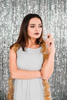Giovane donna elegante che tiene vetro vicino orpello