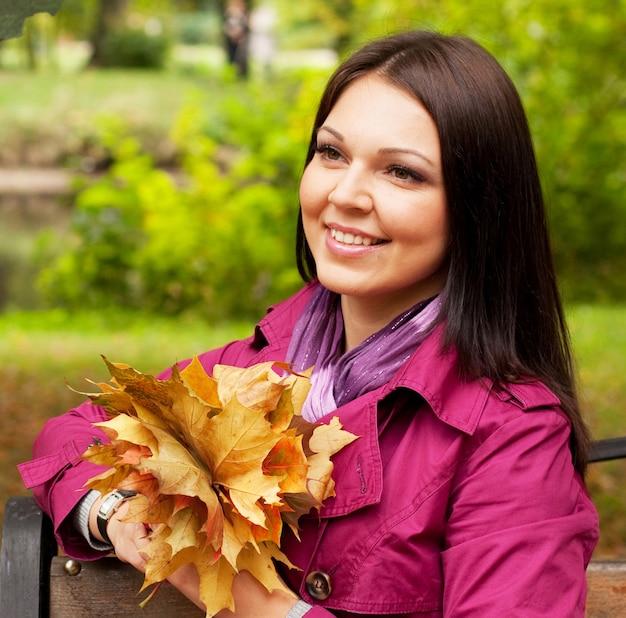 Giovane donna elegante con foglie d'autunno