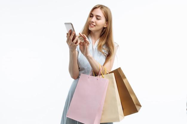Giovane donna elegante, con sacchetti regalo, in posa nelle mani del telefono