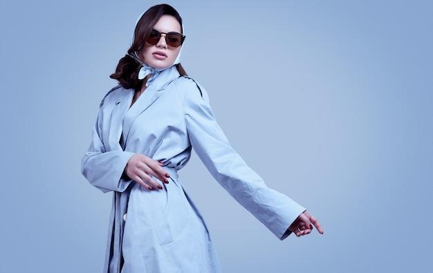 Giovane donna elegante del brunette in cappotto e scialle che propongono nello studio