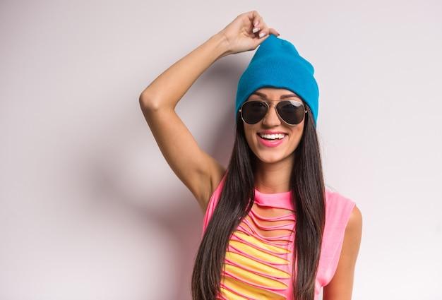 Giovane donna elegante e sorridente in berretto blu e occhiali da sole.