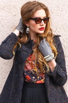 Giovane donna elegante in abito autunnale alla moda di lusso in posa vicino al muro urbano, indossa un cappotto accogliente, alcol floreale e occhiali da sole vintage, ha un trucco luminoso e lunghi capelli biondi.