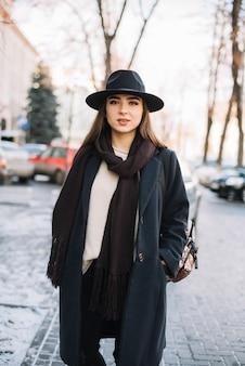Giovane donna elegante in cappello e cappotto con la sciarpa sulla via