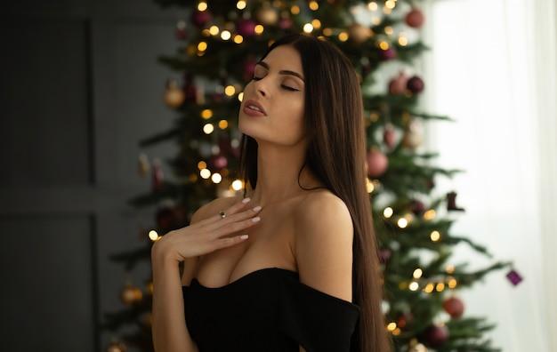Giovane donna elegante in vestito da sera nero che posa nell'interno.