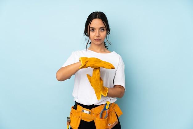 Giovane donna elettricista sul gesto di timeout fabbricazione blu