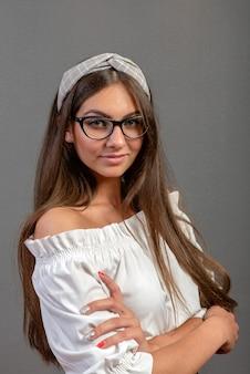 Giovane donna emozionale con gli occhiali su fondo scuro