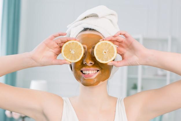 Giovane donna emozionale in asciugamano bianco sulla testa e con la maschera facciale e le metà del limone maturo su spazio bianco. foto di donna che riceve trattamenti spa. concetto di bellezza e cura della pelle