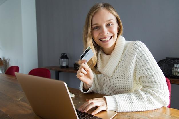Giovane donna emozionante che fa compera online a casa