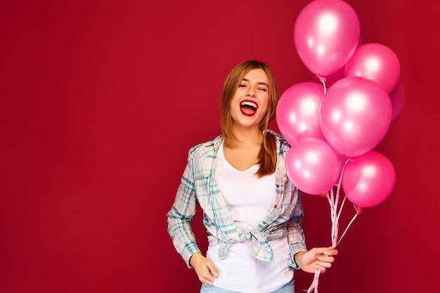 Giovane donna emozionante che posa con gli aerostati rosa