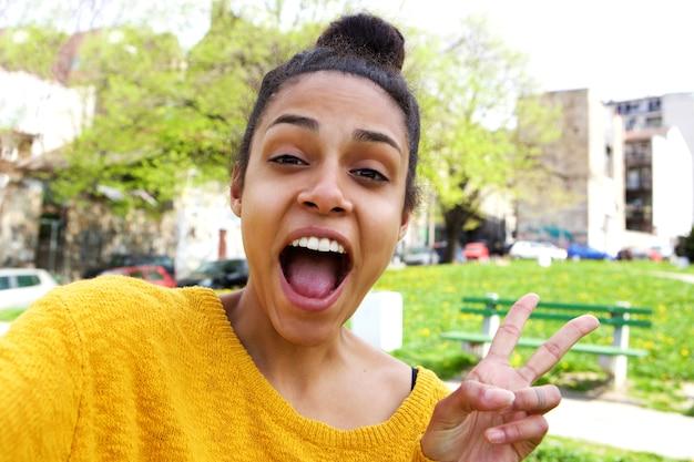 Giovane donna emozionante che prende selfie con il segno di pace