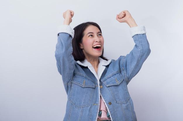 Giovane donna emozionante sorridente asiatica che mostra la sua mano con l'espressione che ritiene sorpresa e stupita, ragazza caucasica felice positiva che indossa il ritratto blu dell'abbigliamento casual