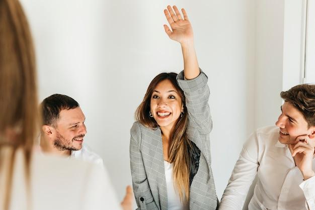 Giovane donna entusiastica con la mano sollevata