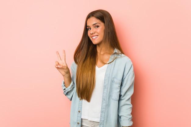 Giovane donna esile allegra e spensierata che mostra un simbolo di pace con le dita.
