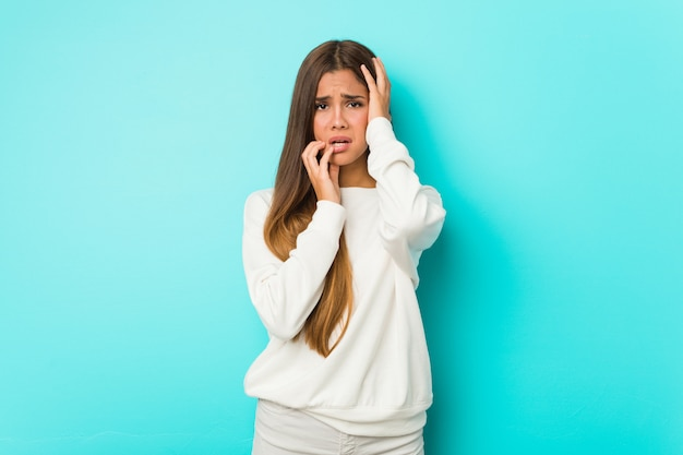 Giovane donna esile che geme e piange sconsolata.