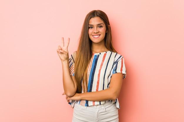 Giovane donna esile che mostra numero due con le dita.