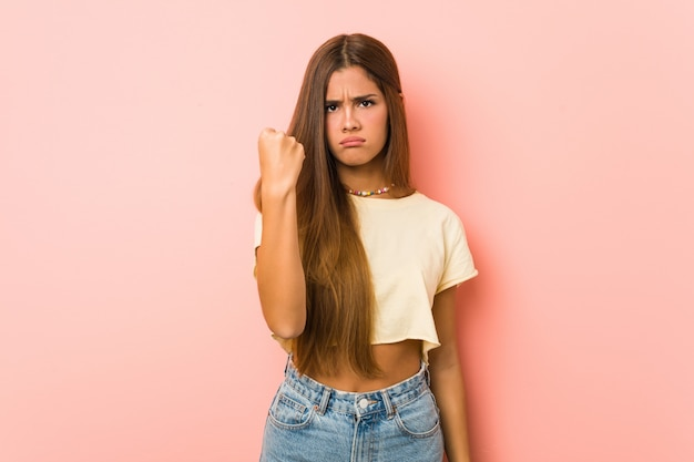 Giovane donna esile che mostra pugno alla macchina fotografica, espressione facciale aggressiva.