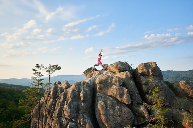 Giovane donna esile che sta con le mani sollevate nella posa di yoga sopra la montagna rocciosa