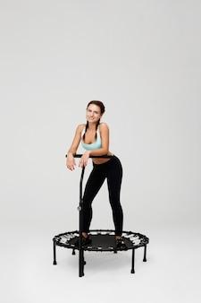 Giovane donna esile con i mazzi che riposano sul rimbalzo dopo l'allenamento