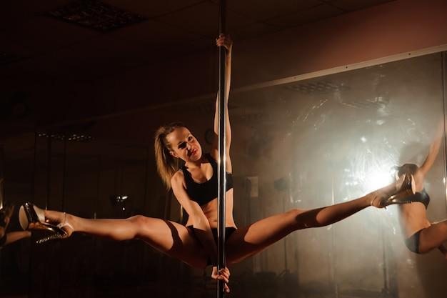 Giovane donna esile di ballo del palo che allunga nell'interno luminoso.