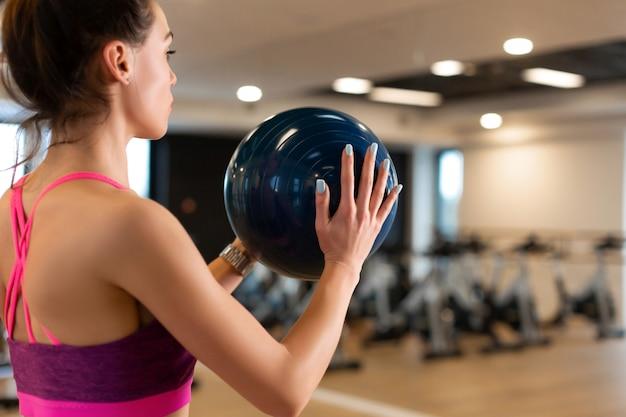 Giovane donna esile in abbigliamento sportivo facendo ginnastica in palestra con medball