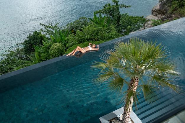 Giovane donna esile in costume da bagno che si rilassa sullo stagno di infinito tropicale del bordo. palme intorno e acqua cristallina. resort di lusso vista aerea