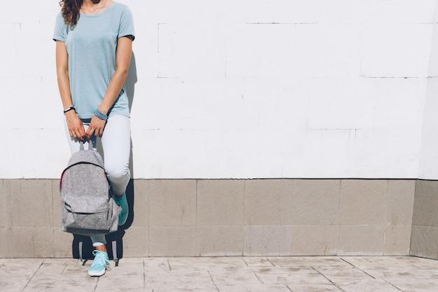 Giovane donna esile in jeans e t-shirt in piedi contro un muro bianco con uno zaino in mano