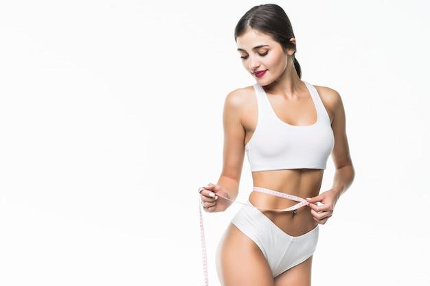Giovane donna esile in mutandine con la misura sulla parete bianca