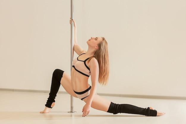 Giovane donna esile poledance che allunga in biancheria
