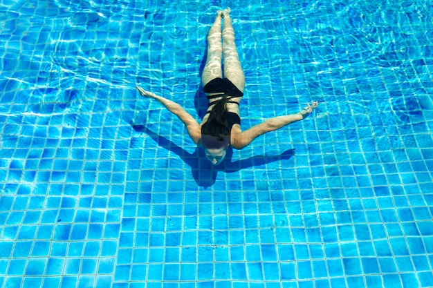 Giovane donna esile sexy che si rilassa nella piscina con acqua blu di cristallo