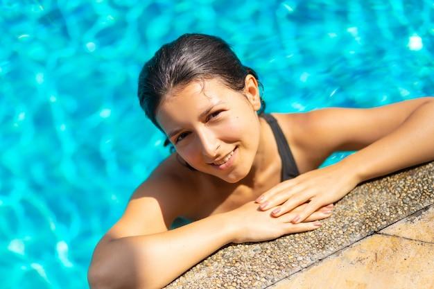 Giovane donna esile sexy che si rilassa nella piscina tropicale con acqua blu di cristallo nel giorno di estate caldo
