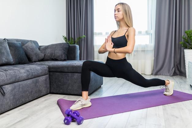Giovane donna esile sicura risoluta che fa gli esercizi sulla stuoia che guarda dritto a casa