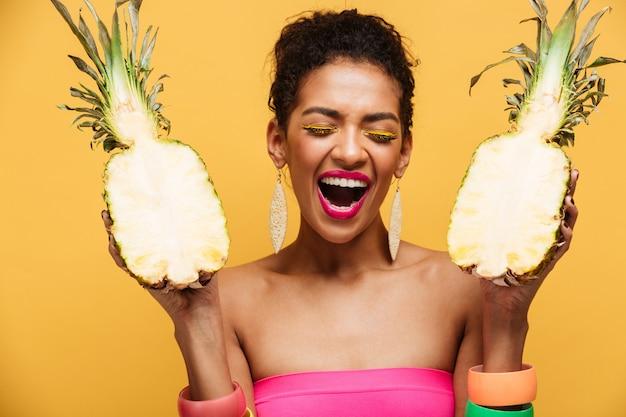Giovane donna estatica con l'acconciatura afro e il trucco variopinto che tengono due metà dell'ananas appetitoso fresco isolato, sopra la parete gialla