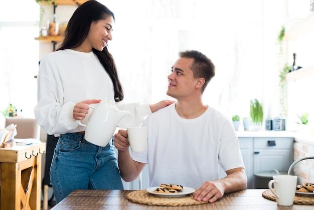 Giovane donna etnica che versa in tazza per il ragazzo