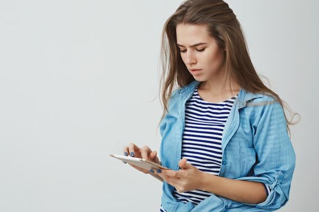 Giovane donna europea alla moda moderna alla moda dall'aspetto serio che tiene compressa digitale