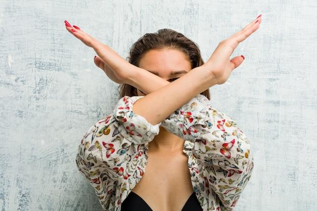 Giovane donna europea che indossa un bikini mantenendo due braccia incrociate, concetto di negazione.