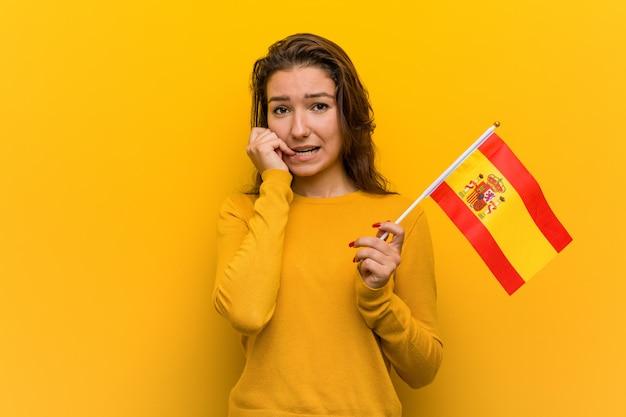 Giovane donna europea che tiene le unghie mordaci di una bandiera spagnola, nervose e molto ansiose.